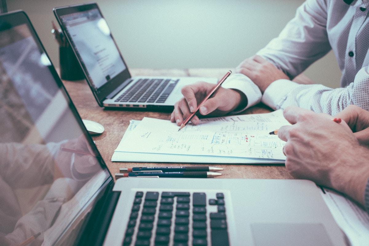 Detalhe de mãos de executivos analisando um papel com gráficos