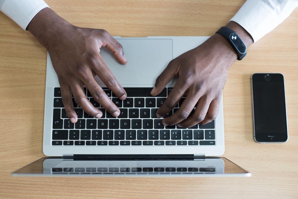 Homem digitando em laptop