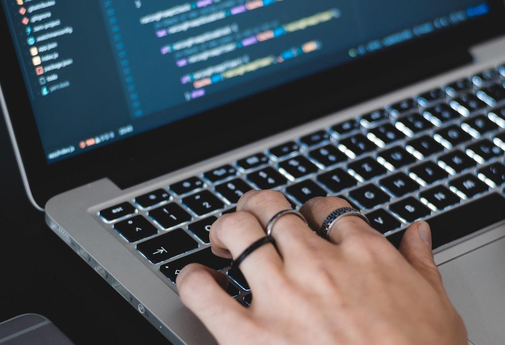 Mãos digitando em laptop