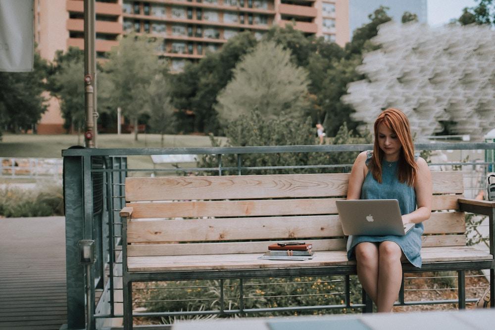 Mulher com laptop ao ar livre