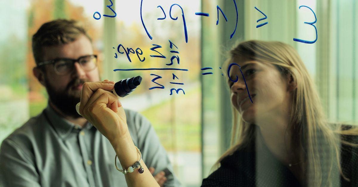 Mulher escrevendo algoritmo em lousa transparente