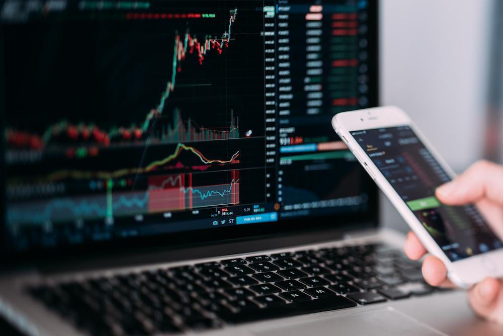 Laptop e celular mostram informações do mercado financeiro
