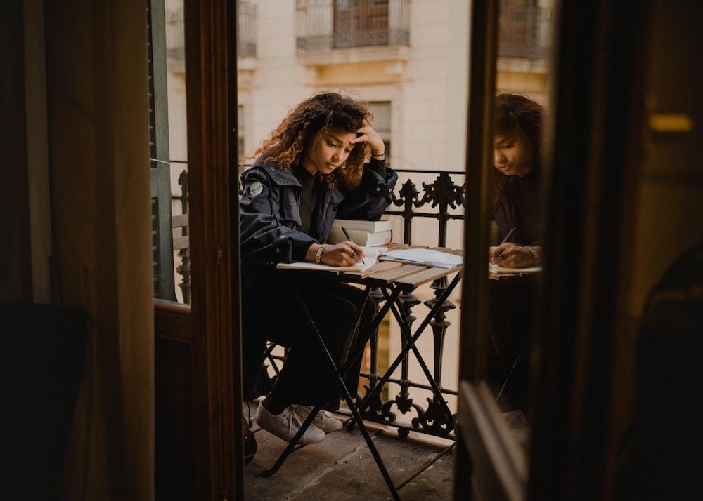 Jovem mulher estudando com laptop ao ar livre em uma varanda