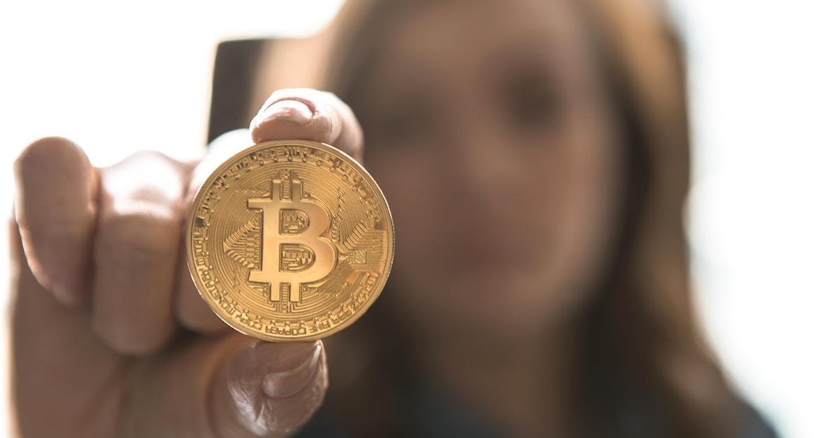 Pessoa segurando símbolo de Bitcoin